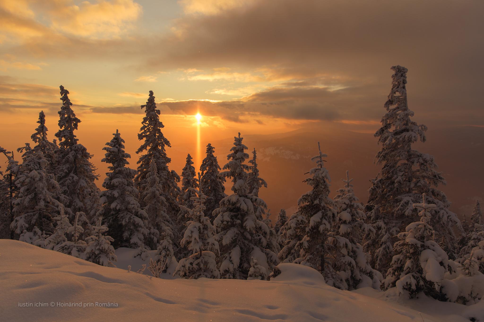 Peisaj de iarnă, apus de soare in Hășmaș, Romania